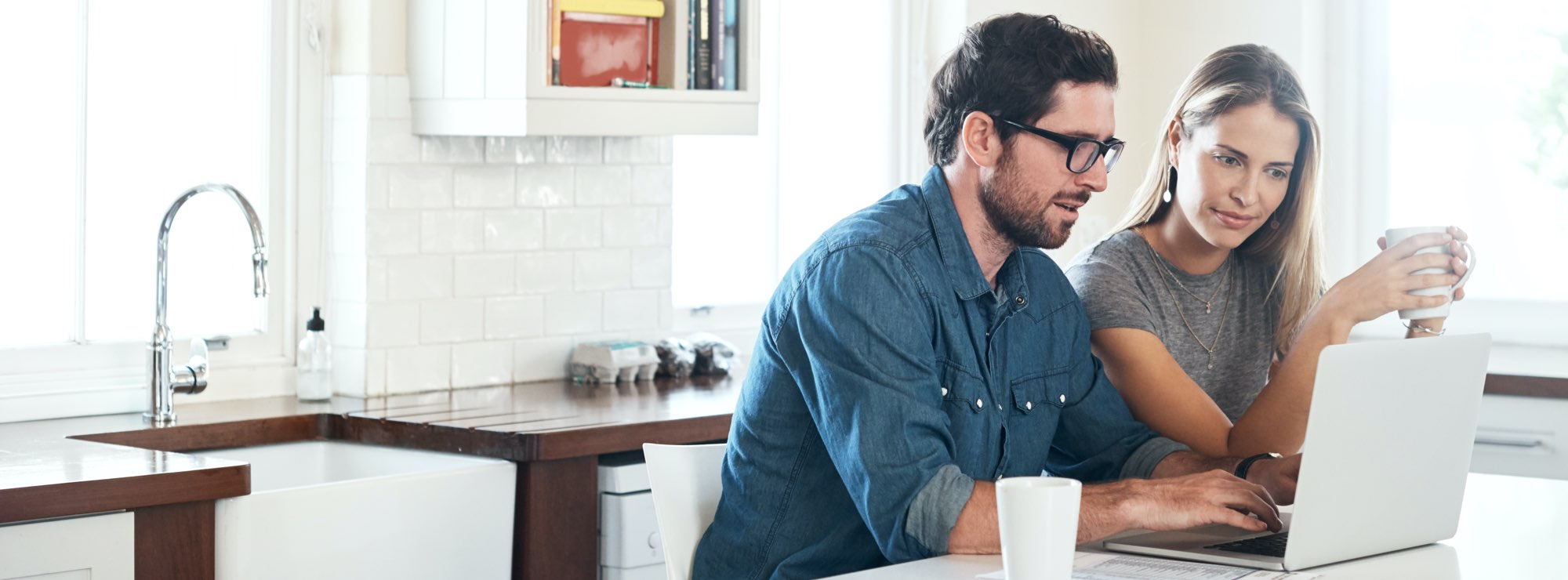 Couple checking on laptop if they're eligible for car finance